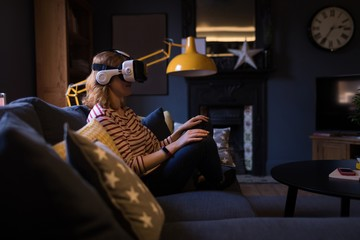 Woman sitting on sofa and using her virtual reality headset
