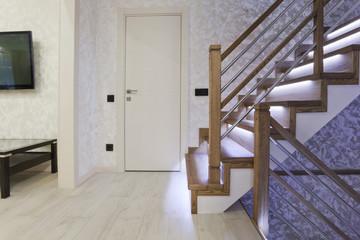 Светлый интерьер и дубовая лестница с подсветкой
