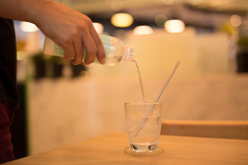 Waiter pouring water from the bottle in the glass