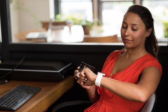 Female executive checking time on smartwatch while having coffee