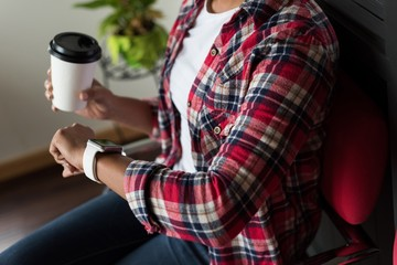 Female executive using smartwatch while having coffee