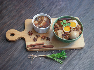 """Pork stew with egg and fried tofu, boiled in brown sauce in white bowl on old brown wooden table background. (Thai food called """" Pha-lo"""")."""