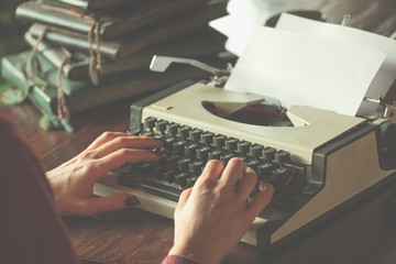 Woman writing on the vintage typing-machine. Shallow depth of field on the hands.