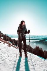 Frau wandert mit Schneestöcken im Schnee