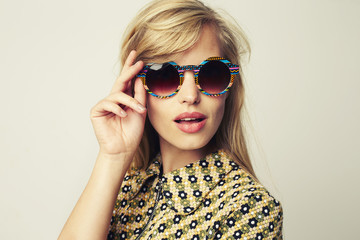 Glamour girl in shades looking to camera, studio