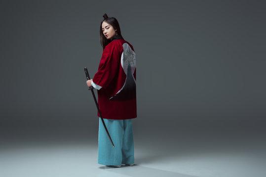 back view of samurai in kimono holding katana and looking at camera on grey