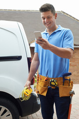 Electrician With Van Texting On Mobile Phone Outside House