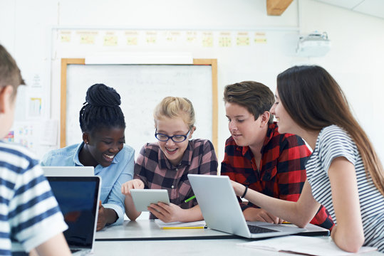 Group Of Teenage Students Collaborating On Project In IT Class