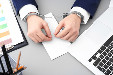 Businessman in handcuffs with bribe at table, closeup