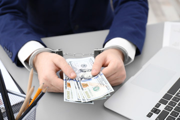 Businessman in handcuffs holding bribe at table, closeup