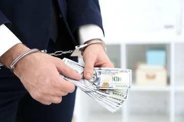 Businessman in handcuffs holding bribe indoors, closeup