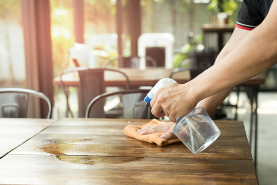 Waiter cleaning the table with Disinfectant Spray