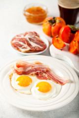 Fried eggs, bacon, a toast, a persimmon