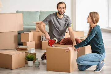 Young couple packing moving boxes, indoors
