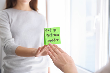 """Woman sticking note with phrase """"Autism spectrum disorder"""" on mirror indoors"""