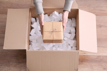 Woman taking gift box out of parcel indoors