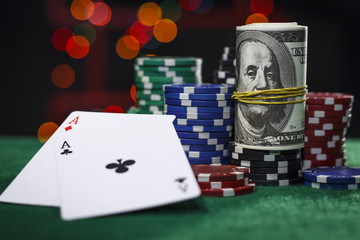 Poker chips, dollars and a pair of aces