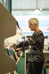 Senior woman selecting book from book shelves