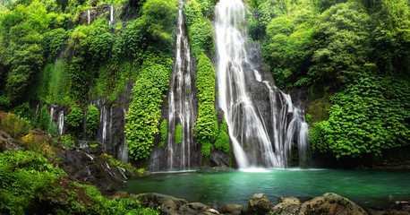 Poster de jardin Cascades Jungle waterfall cascade in tropical rainforest with rock and turquoise blue pond. Its name Banyumala because its twin waterfall in mountain slope