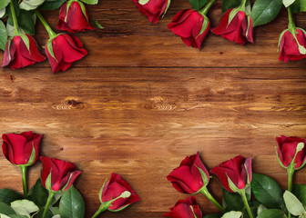 Vertical, top down aerial view of roses lying on natural brown wooden planks background.