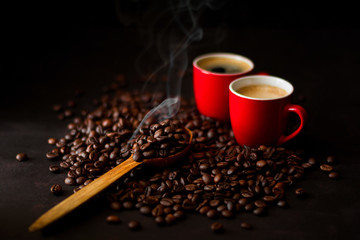 Two red cups of espresso with coffee beans on dark wooden background. Smoke taking away from coffee seeds