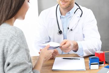 Wizyta u lekarza. Pacjentka w gabinecie lekarskim. Lekarz wpisuje zalecenia i recepty.