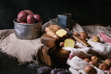 Variety of raw uncooked organic potatoes different kind and colors red, yellow, purple on wooden cutting board with kitchen towels over black table. Dark rustic style