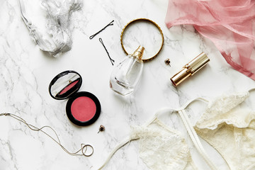 Overhead view of female lace lingerie, perfume, lipstick, blushes and jewelry items on white marble background. Top view, text space. Beauty routine concept