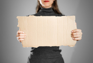A young girl in a grey jacket holding a piece of cardboard. Prepared for your text
