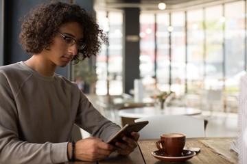 Man using digital tablet in cafeteria