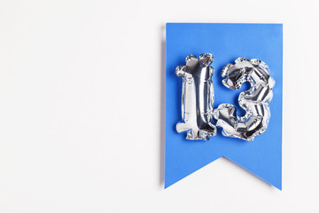 Number 13 silver balloon celebration number on a blue banner