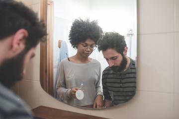 young multiethnic couple indoor bathroom brushing teeth