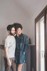 young multiethnic couple indoor looking away serene