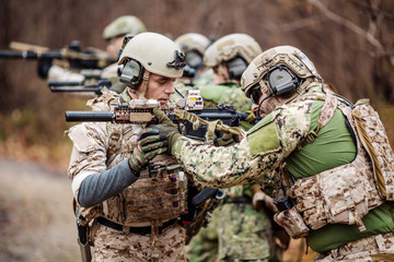 Instructor with soldier aiming machine gun at firing range.