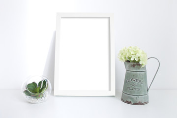 A4 white frame on desk with plant and vintage jug