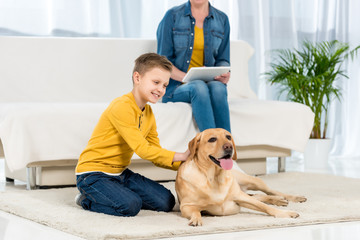 happy kid petting dog on floor while mother using tablet on couch
