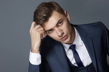 posing beautiful male model in blue suit and waistcoat and tie