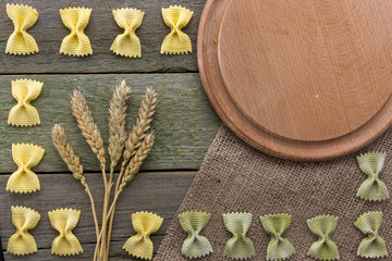 Spike of wheat and pasta, on a wooden background, with space for text