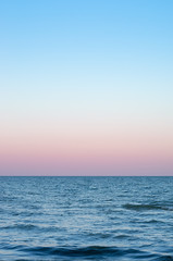 Wall Mural - pink sky of sunset on the sea horizon, vertical composition.
