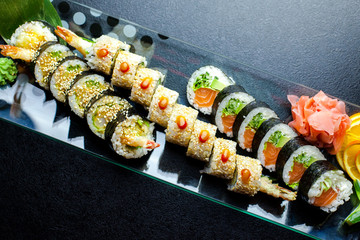 Sushi rolls set served on glass plate on dark background