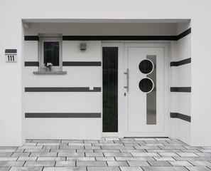 Moderner Eingang eines Hauses mit Haustür Fenster und Betonpflaster -  Modern entrance of a house with front door window and concrete pavement
