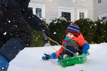 adorable toddler boy sledding in snow