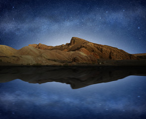 Foto auf Leinwand Reflexion rocky hill reflected in water under a starry night sky