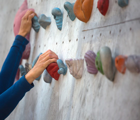 Hand on a hold of the artificial climbing wall
