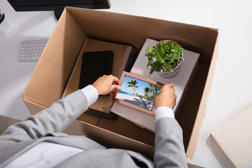 Businesswoman Packing Picture Frame In Cardboard Box