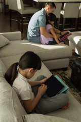 Girl using digital tablet with her father in living room