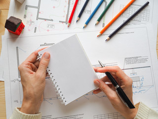Notebook with copy space in the hands on the background of an architectural project.
