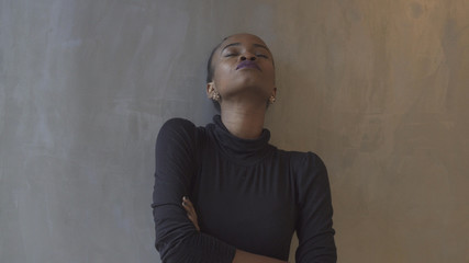 Portrait of the attractive isolated african girl leaning on the gray wall with closed eyes and arms crossed.