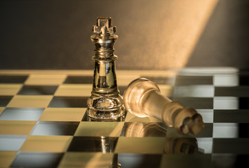 Crystal king defeats frosted king on the chess board with sunlight background.