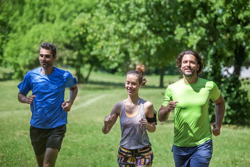 Woman and two young men running in the park